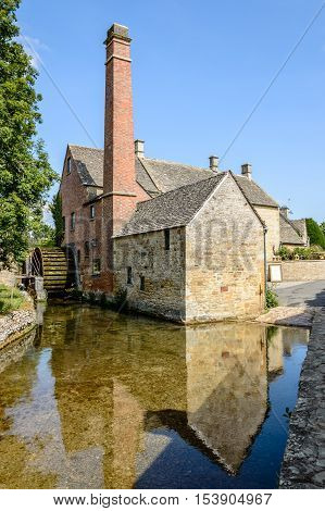 Old watermill in Lower Slaughter in the Cotswolds reflected on the water a blue sky day