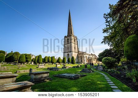 Painswick UK - August 17 2015: St Mary's Church and churchyard a blue sky day. Painswick is a town in the Cotswolds originally the town grew on the wool trade.