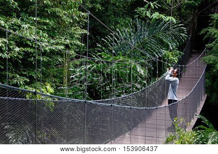 Male birdwatcher standing on wooden bridege, surrounded by jungle.