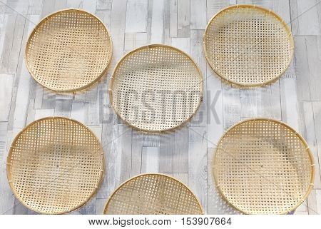Bamboo Handicraft Wicker Threshing Baskets Hanging on The Wood Wall.
