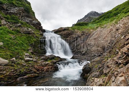 Summer mountain landscape of Kamchatka: beautiful view of picturesque waterfall in Mountain Range Vachkazhets. Eurasia Russian Far East Kamchatka Peninsula.