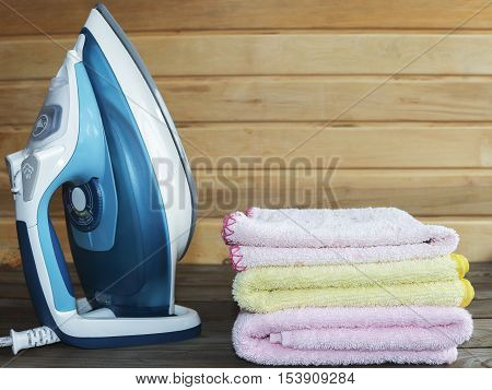 Iron, electric tool. Ironing colorful towels on wooden table