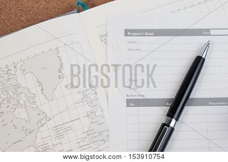 World map diary and pen with copyspace on wooden background. World map and diary project plan and goal for planning a trip. Diary notebook for travel concept.