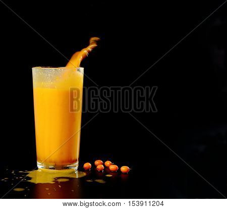 juice sea-buckthorn with splashes,squirt and drops on a black background