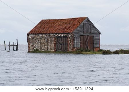 Flood tide that surged in at Thornham harbour in October , this shows the harbour barn surrounded by the sea.