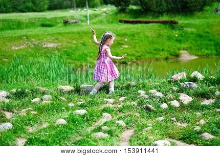 Adorable little girl walking on the ro?ks by a pond in sunny park