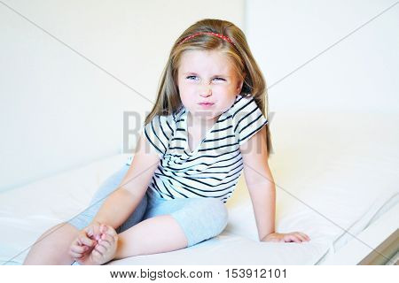 Portrait of little angry preschooler girl at home