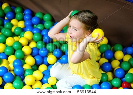 Happy Little Girl Playing At Colorful Plastic Balls Playground