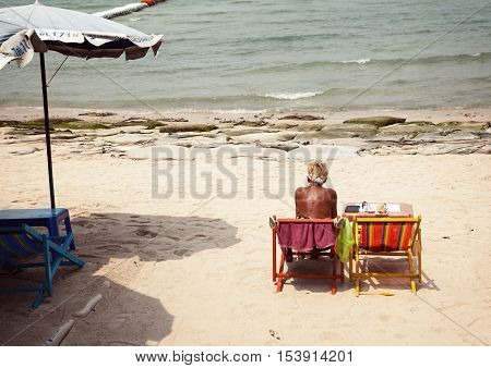 Pattaya Thailand - March 24 2016: Old woman at the dirty messy sunny beach.