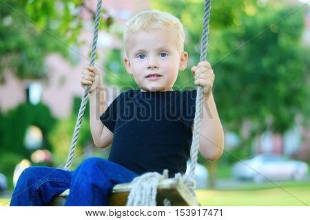 Adorable Little Blonde Boy Having Fun At The Playground.