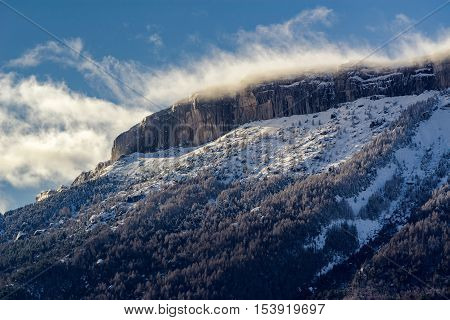 Ceuze mountain and cliff with  blowing snow in Winter. Hautes Alpes, Southern French Alps, France