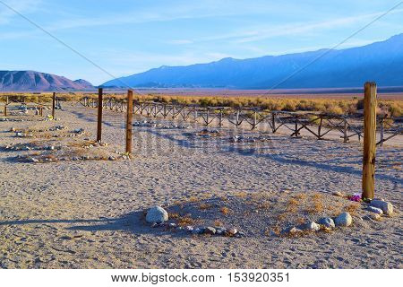 Rural cemetery with wooden headstones and graves marked by rocks taken in the Great Basin Desert