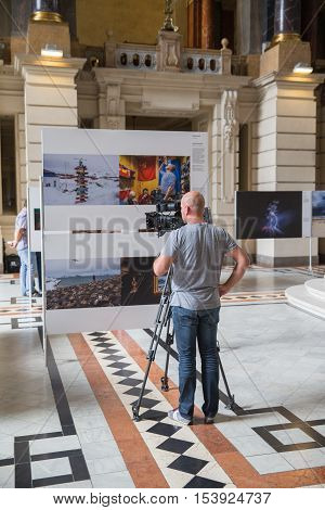 Budapest, Hungary - September 29, 2016. World Press Photo -popular annual exhibition. Ethnographic Museum interior. Operator is filming at the exhibition. Make movie. Operator make film.