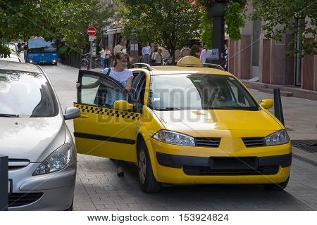 Budapest, Hungary - September 29, 2016. The young girl is taking a taxi. The young girl calculated with a taxi. Yellow taxis