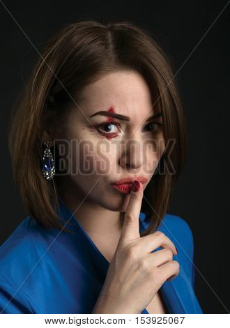 A portrait of close up of an  girl. Holding her finger, showing to keep silent.