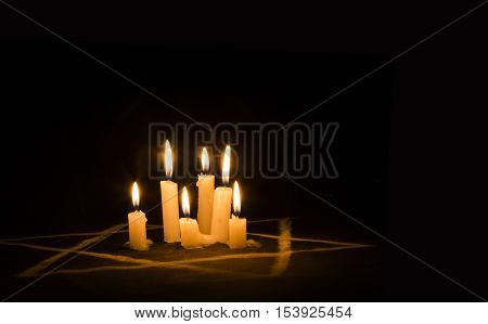 Six Burning Candles And The Star Of David Against A Black Background, Text Yom Hashoah, We Will Neve