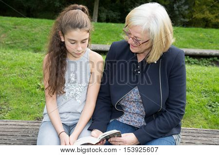 Grand Mother With The Grand Daughter In Autumn Park