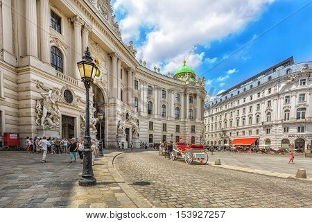 VIENNA AUSTRIA - JUNE 25 2016: Hofburg Palace seen from Michaelerplatz on sunny day with tourists and people. Vienna. Austria.