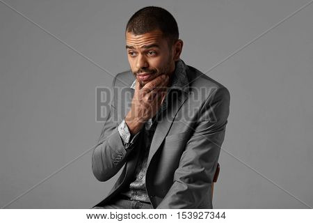 thoughtful black man thinking in gray blazer isolated on studio gray background
