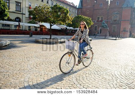 Cute young brunette in sunglasses rides by bicycle on a paved pavement. Solar morning. Beautiful buildings of the ancient European city cozy cafes green trees. Girl in a good mood she smiles.