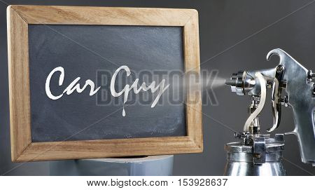 Car guy sign being sprayed painted on blackboard.