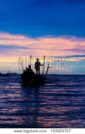 silhouette of fisherman on the boat in sunset time.