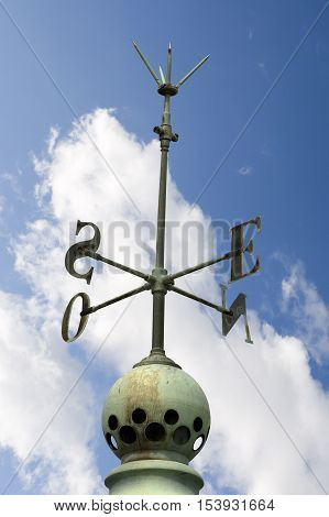 Old cardinal points (cardinal directions north east south west) on a roof with a lightning rod on blue sky with clouds