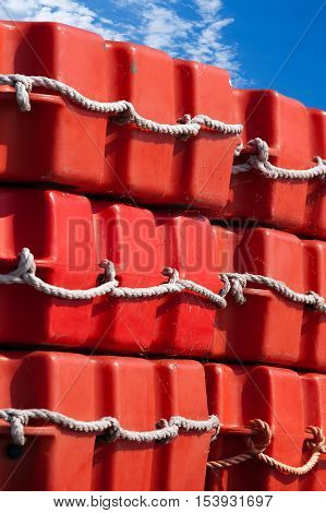Detail of a stack of red liferafts (life rafts) with ropes on a blue sky with clouds