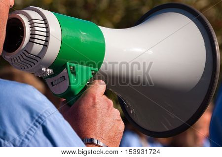 Detail of a scout leader shouting through a green and white megaphone