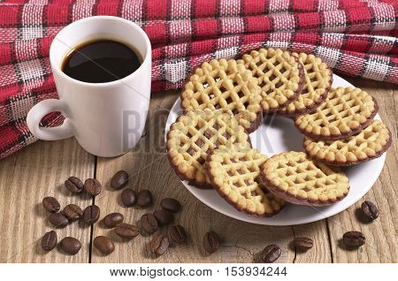 Cup of hot coffee and cookies with chocolate on old wooden table covert red tablecloth