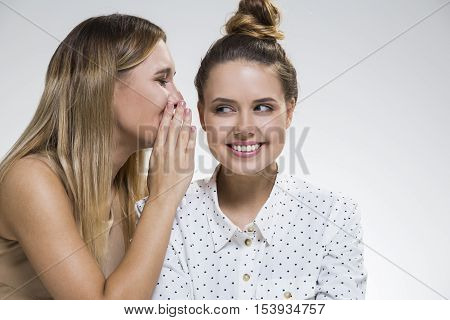 Two Girls Gossiping, One Is Intrigued