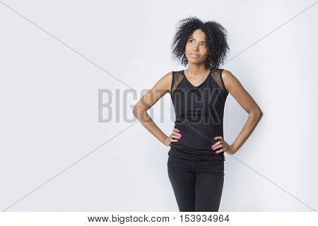 Portrait of African American girl thinking and looking into distance while standing with her hands on the waist. Concept of contemplation. Mock up