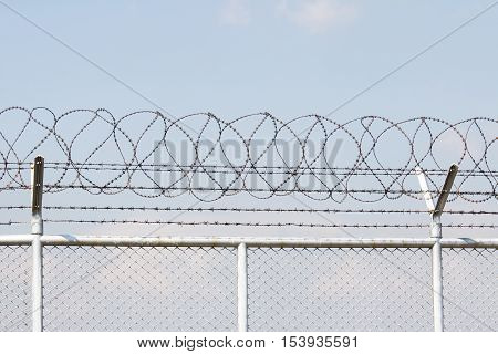 Barbed wire fence blocking the entrance to the airport and sky background