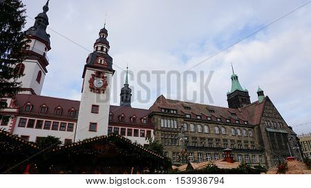 At the Christmas market in Chemnitz in Saxony Germany; illumined booths the Old and New City Hall in the background the tower of the church St. James