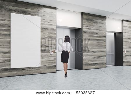 Woman is waiting for elevator. Two of them are closed and situated in corridor with wooden walls and poster. Concept of office center life. 3d rendering. Mock up.