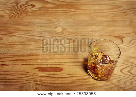 Glass of Whiskey with ice on old wooden table