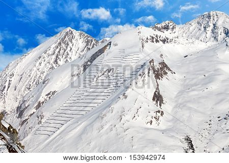 Photo of snowy mountains with avalanche protection barriers