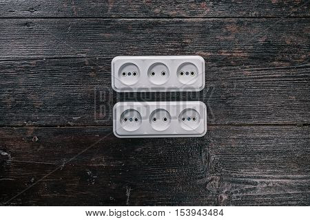 White triple electric sockets on the dark wooden surface