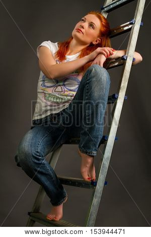 Beautiful young red-haired girl leaning on a ladder on a gray background