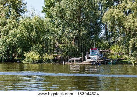 Boat on the riverside between willows in Danube Delta