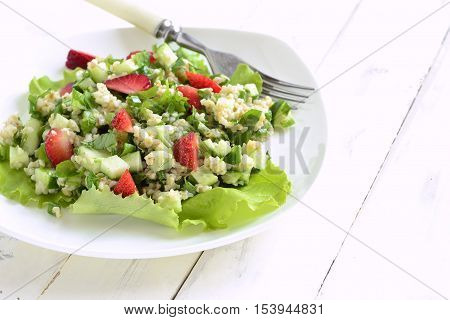 Tabbouleh with strawberries bulgur and vegetables, copy space