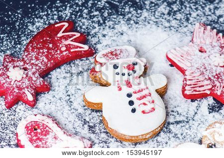 Christmas background decoration. Cinnamon, cookies shape such as heart and star. Flour and spices for a christmas baking on a dark background.