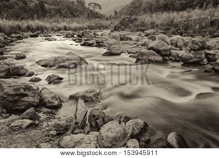 Beautiful Reshi River water flowing through stones and rocks sepia toned Sikkim India. Reshi is one of the most famous rivers of Sikkim flowing through the state and serving water to many local people.