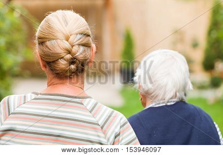 Young carer walking with the elderly woman in the park