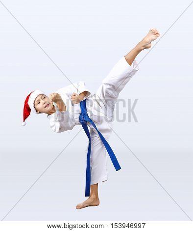 Boy in karategi and hat of Santa Claus hits a kick