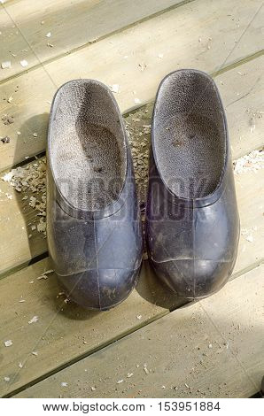 a pair of dirty old black rubber galoshes on a wooden floor green color in the daytime