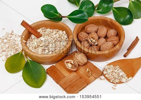 There are with Walnuts and Rolled Oats in the Wooden Plates with Sticks of Sinnamon,Wooden Support,Spoon,Green Leaves,Healthy Fresh Organic Food on the White Background,Top View
