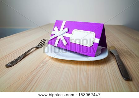 A purple place card in a plate on a wooden background