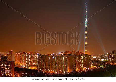 lit by lamps television tower in the night on the background of houses