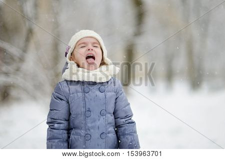 Adorable Girl Catching Snowflakes With Her Tongue